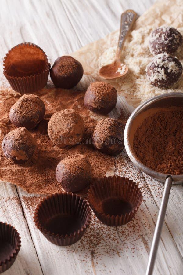 Het bestrooien van de cacaopoeder van chocoladetruffels en notenclose-up Ve stock afbeelding