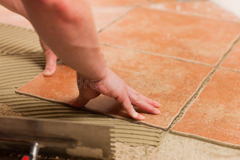Het betegelen van de tegelzetter tegels op de vloer stock fotografie