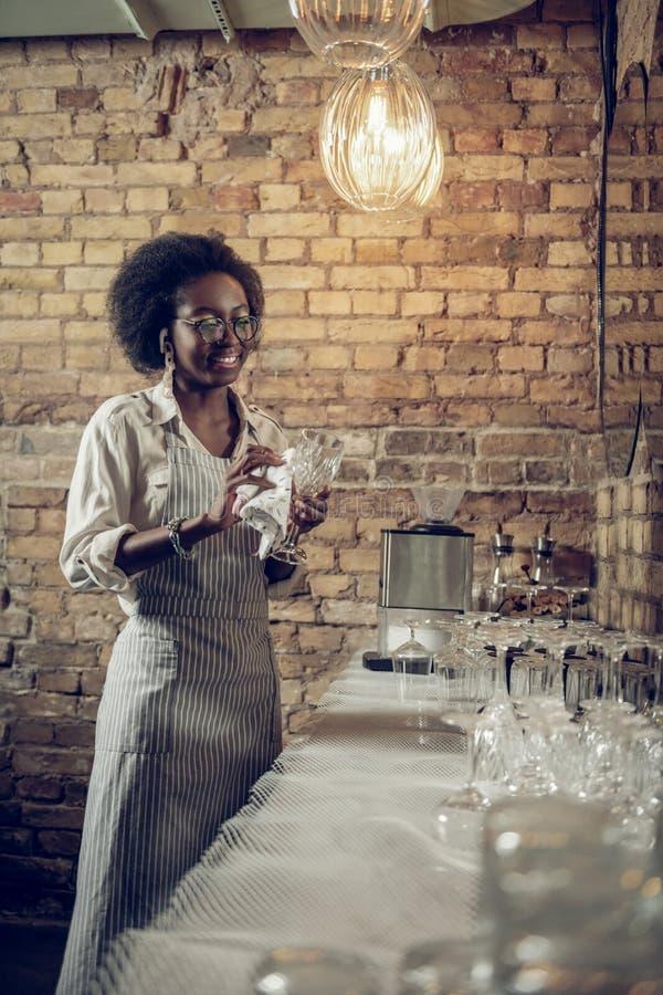 Het betoveren van richtende cheerfully glanzende glazen Afrikaans-Amerikaan bij zolderbar stock afbeeldingen