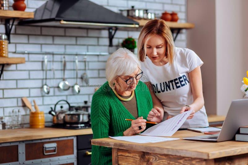 Het betoveren van vrijwilliger die het verouderen de toepassingskernen verklaren van de vrouwen achterstallige lening stock afbeeldingen