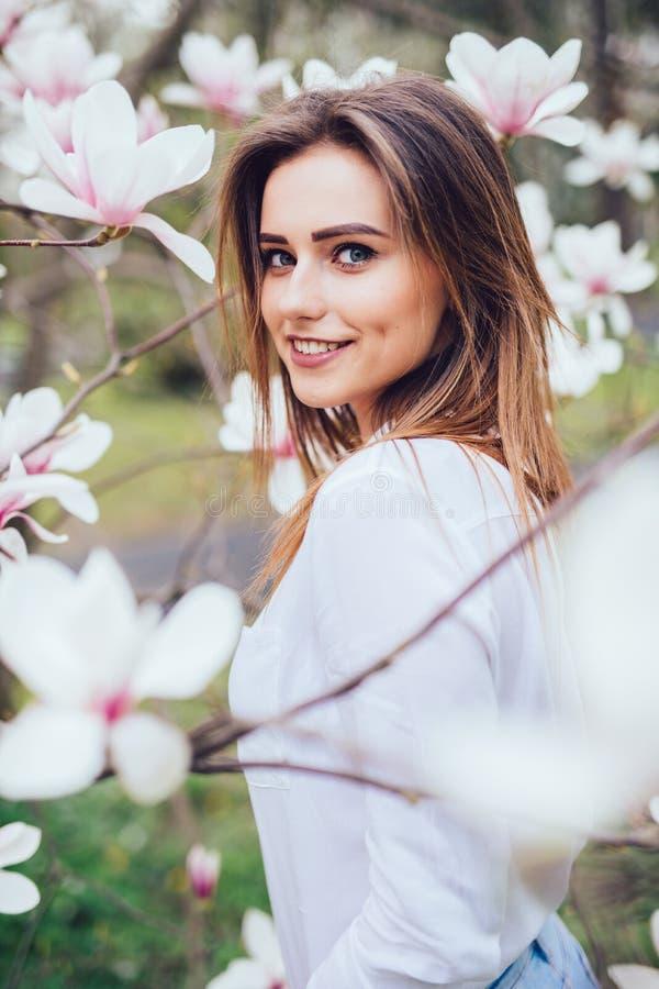 Het Beutyportret van jong meisje dichtbij bloesemmagnolia bloeit in openlucht in de lentepark royalty-vrije stock foto's