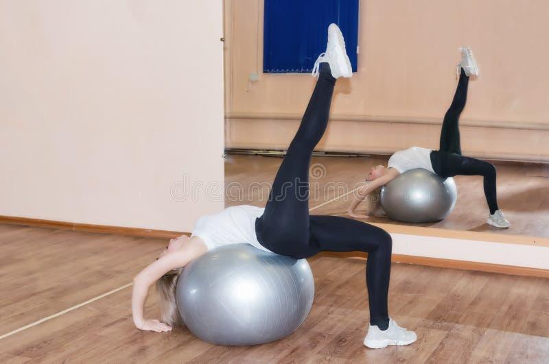 Het bevallige jonge meisje doet geschiktheidsoefeningen op een oefeningsbal stock fotografie