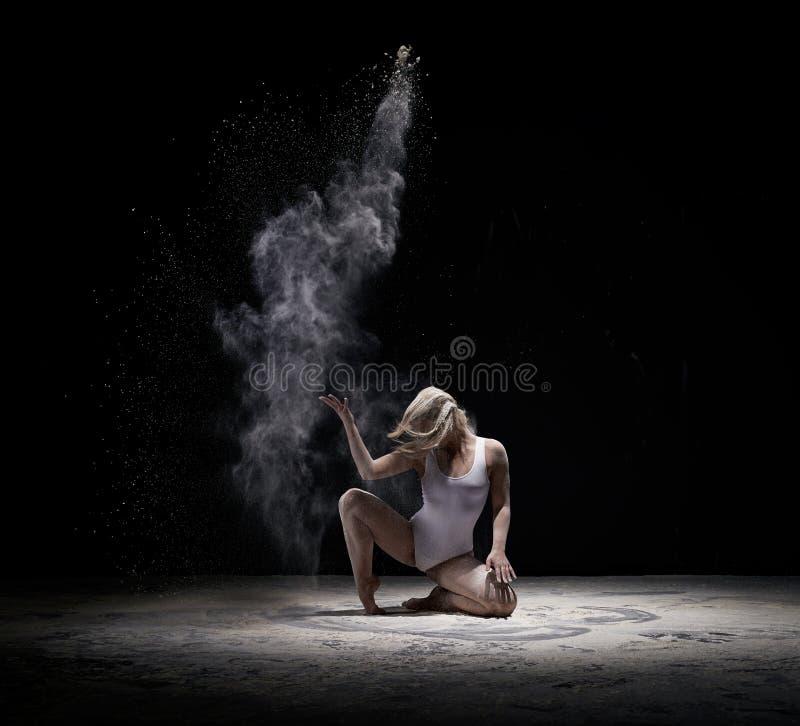 Het bevallige meisje stellen in wolk van wit stof stock foto