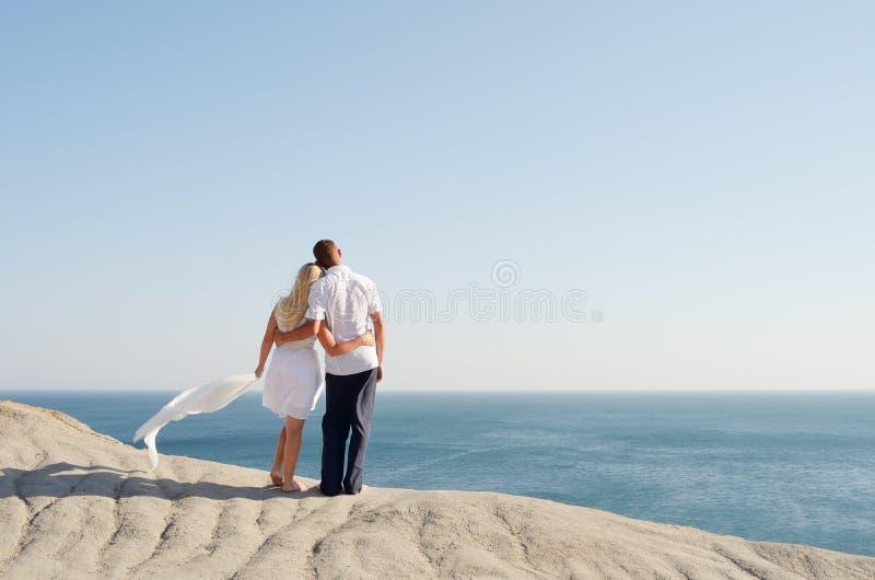 Het bevindende wapen van de man en van de vrouw in wapen op een rots stock foto