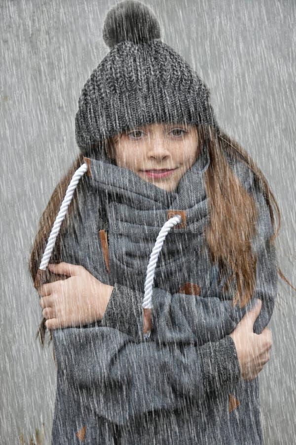 Het bevriezen meisje met bobble hoed die zich in de regen bevinden royalty-vrije stock fotografie