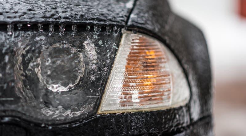 Het bevriezen regenijs met een laag bedekte auto Koplamp en signaallicht op zwarte die auto in het bevriezen regen wordt behandel stock foto