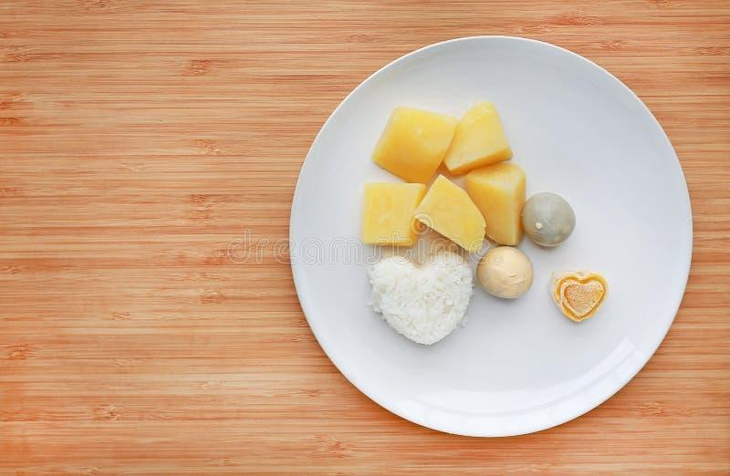 Het bevroren eigengemaakte en ruwe voedsel van het babyvoedsel in witte plaat, Eiaardappel en rijst voor fijngestampt op houten r stock fotografie