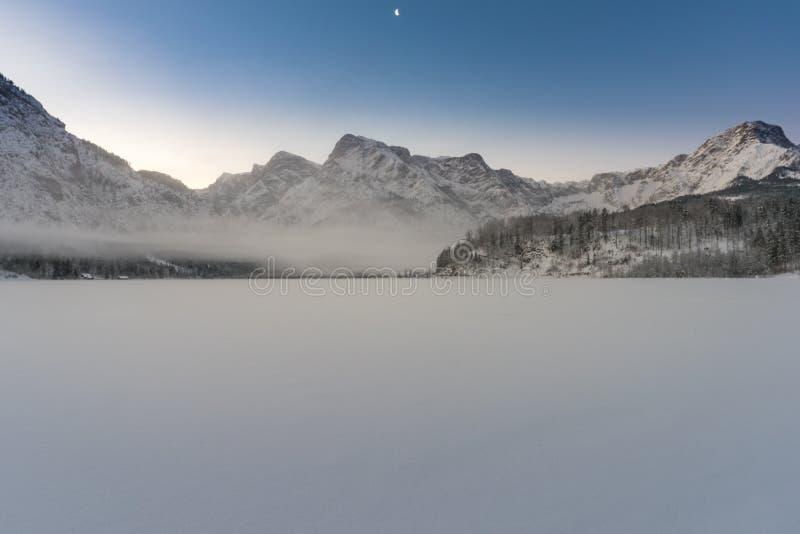 Het bevroren meer Almsee in Boven-Oostenrijk met Zwölferkogel op de achtergrond stock foto