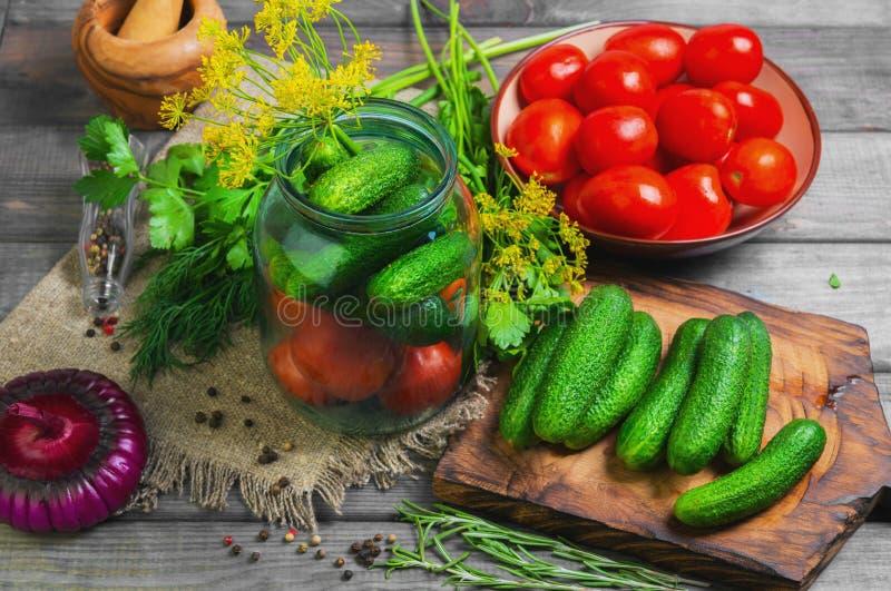 Het bewaren van verse en ingelegde komkommerstomaten royalty-vrije stock fotografie