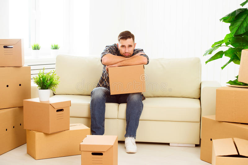 Het bewegen zich aan een nieuwe flat vermoeide mens met kartondozen royalty-vrije stock foto's