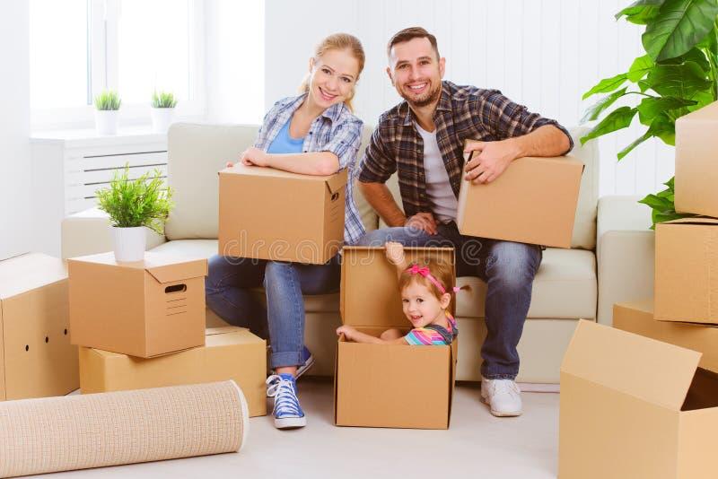 Het bewegen zich aan nieuw huis Gelukkige familie met kartondozen stock foto