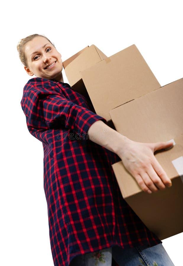 Het bewegen zich aan nieuw huis - glimlachende jonge vrouw met stapel kartondozen stock afbeelding