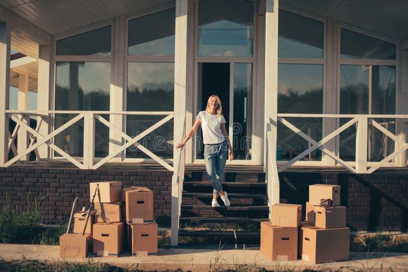 Het bewegen zich aan nieuw huis vrouw die het nieuwe leven beginnen Kartondozen dichtbij trede stock foto