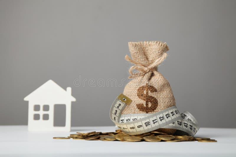 Het bewerken van zak met dollarembleem op gele muntstukken en het meten van band op achtergrond van cijfer van huis Ð ¡ oncept va royalty-vrije stock fotografie