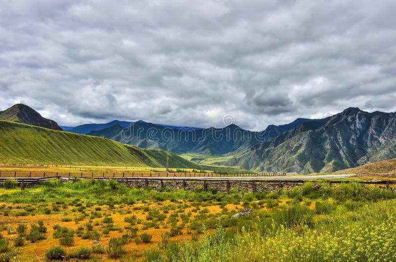 Het bewolkte landschap van de de zomerberg met omheiningen van weilanden langs weg royalty-vrije stock afbeeldingen