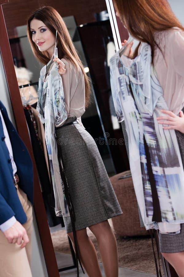 Het bewonderen van de schoonheid van nieuwe kleding stock foto
