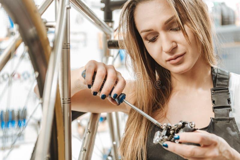 Het bewuste craftswoman charmeren herstellend het pedaal in de workshop royalty-vrije stock foto's