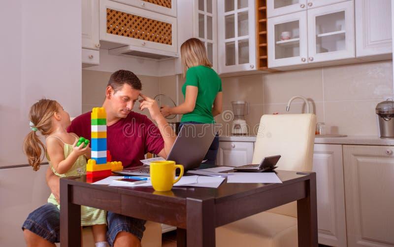 Het bezige Familiehuis met Vader Working As Mother bereidt Maaltijd voor stock foto