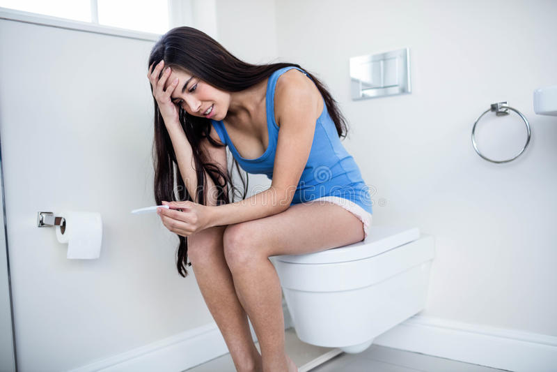 Het bezorgde donkerbruine wachtende resultaat van de zwangerschapstest royalty-vrije stock foto
