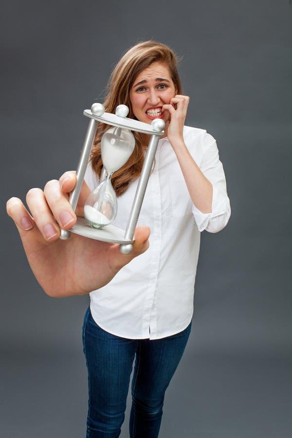 Het bezorgde mooie jonge vrouw panicking bij het houden van een zandloper stock fotografie