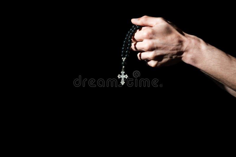 Het bidden handen die een rozentuin met kruis houden stock foto's