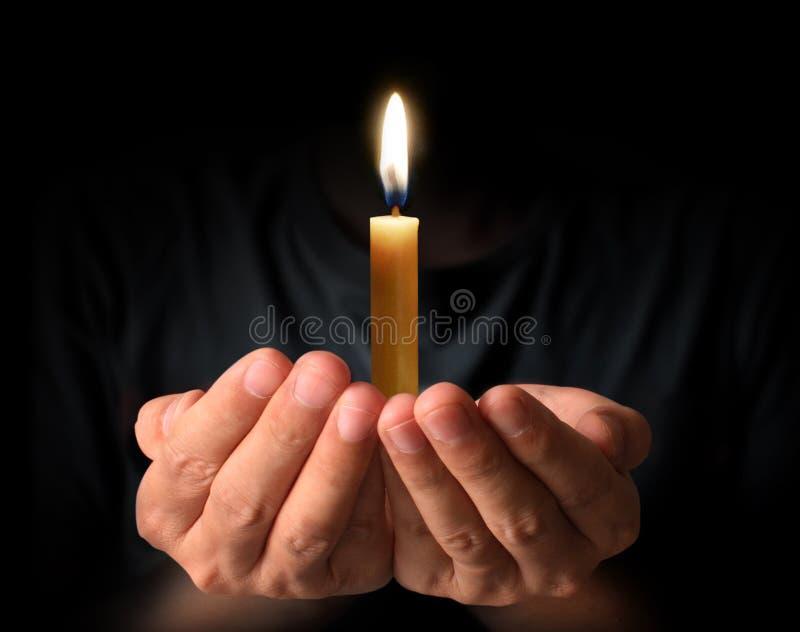 Het bidden Handen met kaars stock fotografie