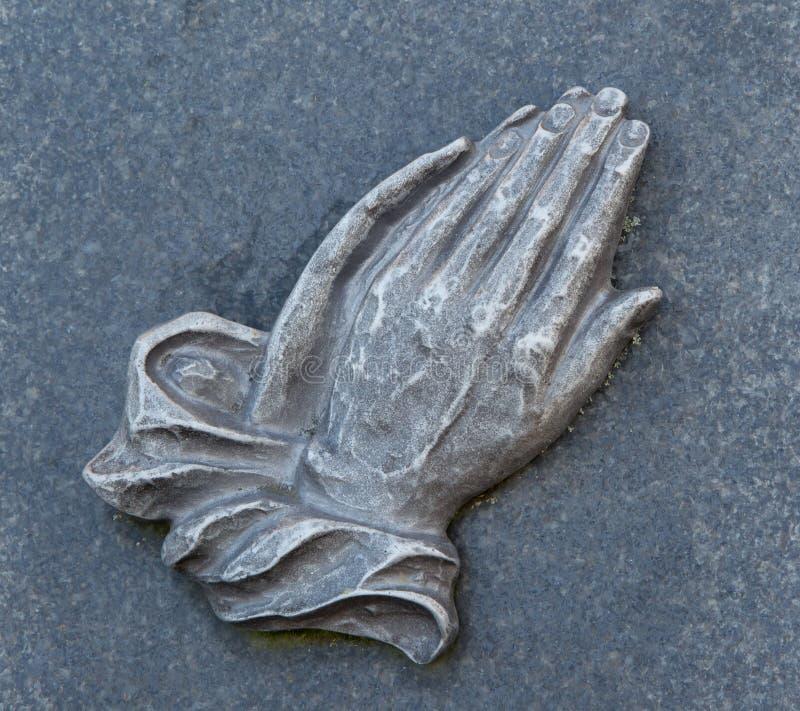 Het bidden handen op het graf stock foto