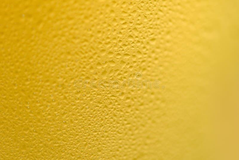 Het bier borrelt glas dichte omhooggaand van het waterdaling van het mokbier op textuurachtergrond stock fotografie