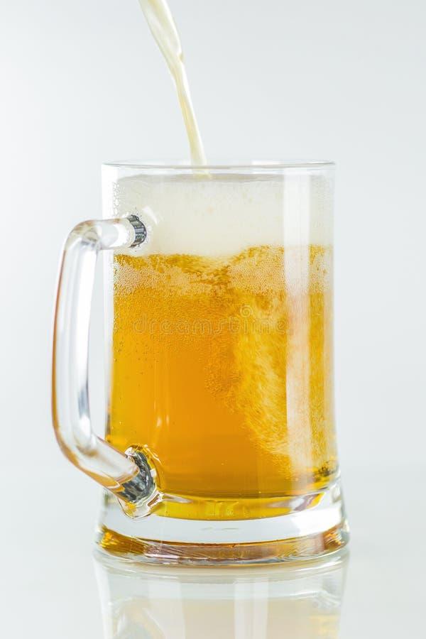Het bier om in glas op een geïsoleerde achtergrond een schuim te gieten neemt op een witte achtergrond toe royalty-vrije stock foto's