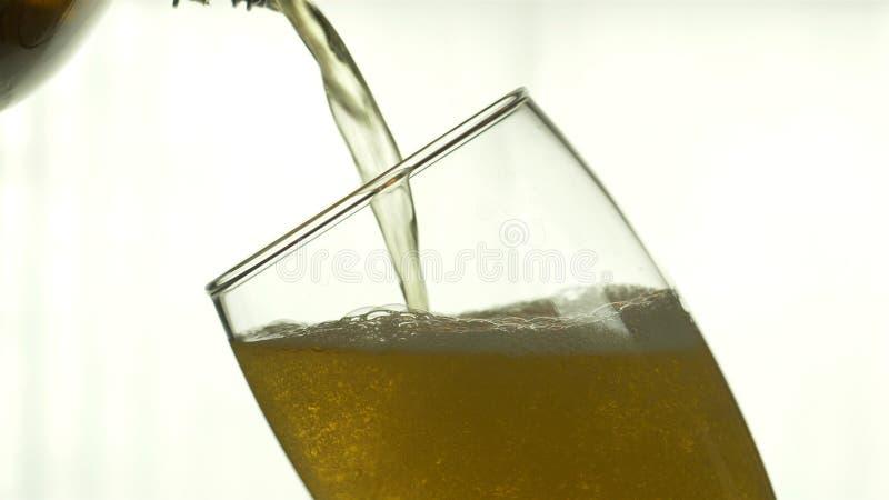 Het bier wordt gegoten in een glas op een ge?soleerde achtergrond Het glas is de zichtbare helft royalty-vrije stock afbeelding