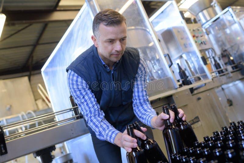 Het bierflessen van de brouwersholding in krat bij brouwerij royalty-vrije stock fotografie
