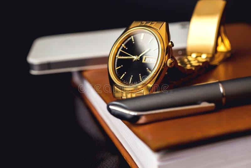 Het bijkomende, gouden horloge van mensen, pen en mobiele telefoon op de leeragenda stock fotografie