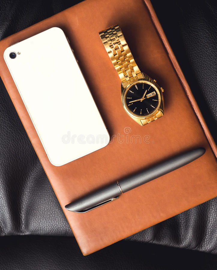 Het bijkomende, gouden horloge van mensen, pen en mobiele telefoon op de leeragenda stock afbeeldingen