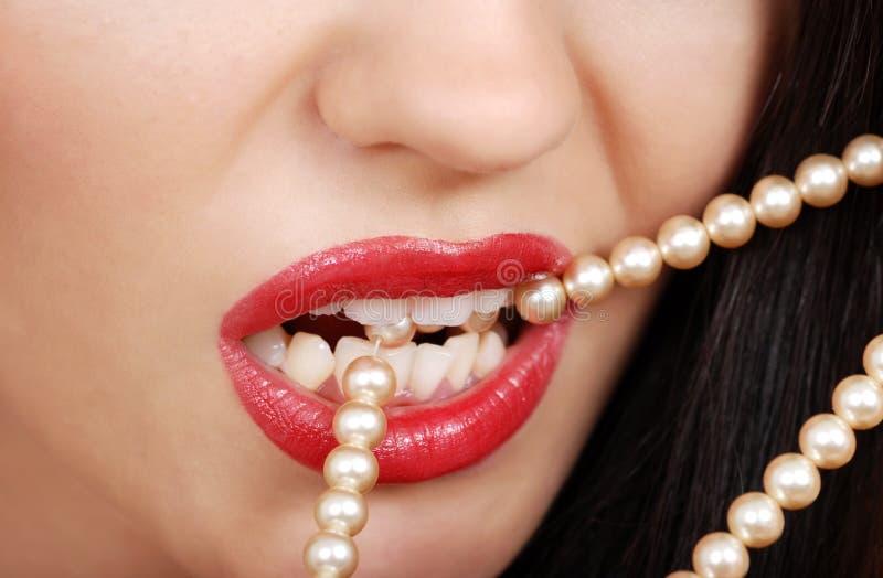 Het bijten van de vrouw parelhalsband met rode lippenstift royalty-vrije stock afbeelding