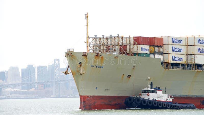 Het bijwonende Vrachtschip MATSONIA van de sleepbootpatriot aan manoeuvre royalty-vrije stock afbeelding