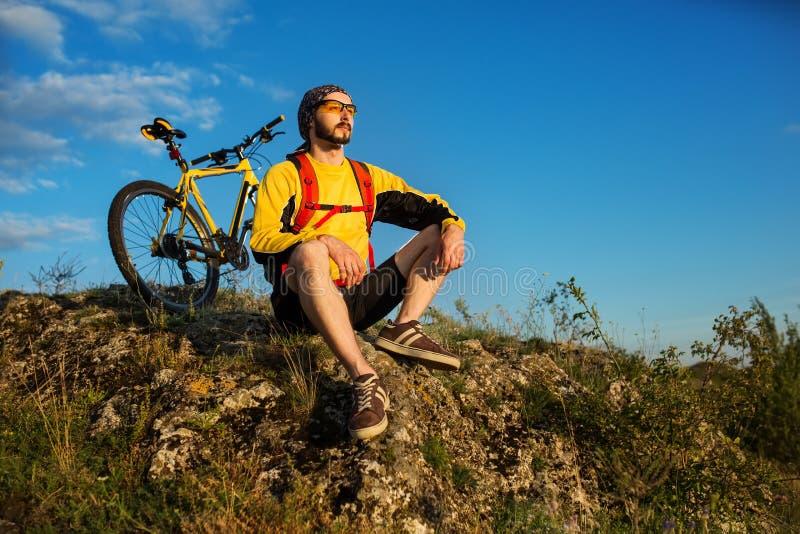 Het biking van de berg onderaan de sleep Toerist met rugzakreis op fiets royalty-vrije stock foto's