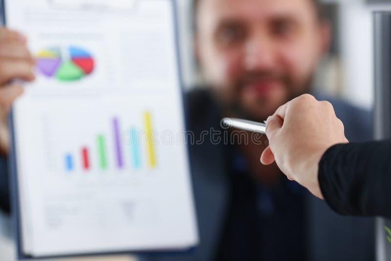 Het bindmiddel van de zakenmangreep in zijn wapens bespreekt met zijn partner hun toekomstig project stock afbeelding