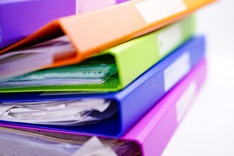 Het Bindmiddelenstapel van de dossieromslag van multikleur op lijst in bureau stock afbeelding