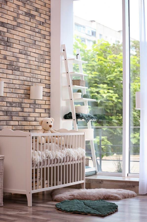 Het binnenland van de babyruimte met voederbak dichtbij muur stock afbeelding