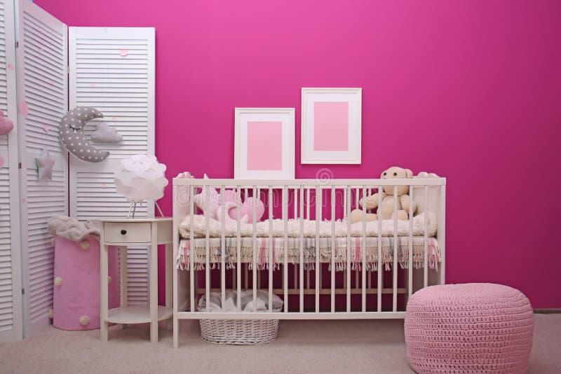 Het binnenland van de babyruimte met voederbak dichtbij muur stock foto's