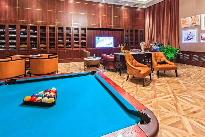 Het binnenland van de de sigarenzitkamer van het Rixoshotel met modern meubilair, het comfortabele plaatsen en een biljartlijst v stock afbeeldingen