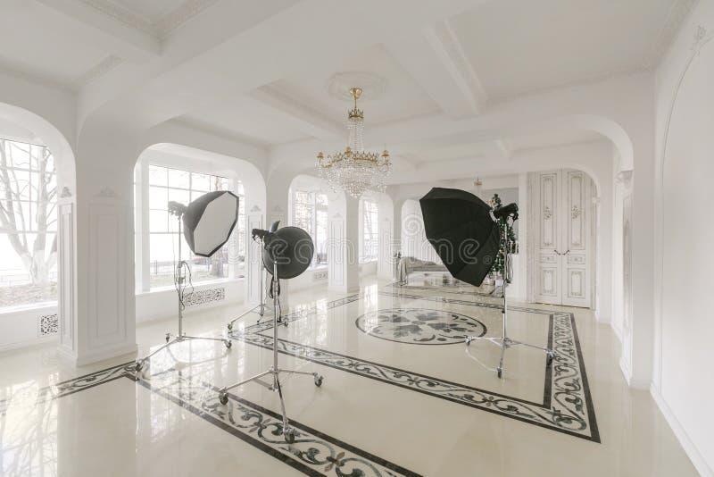 Het binnenland van de fotostudio klassieke luxueuze flats met een witte open haard, een bank, grote vensters en een kroonluchter royalty-vrije stock foto's