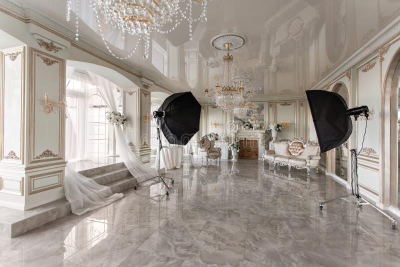 Het binnenland van de fotostudio klassieke luxueuze flats met een witte open haard, een bank, grote vensters en een kroonluchter stock afbeeldingen