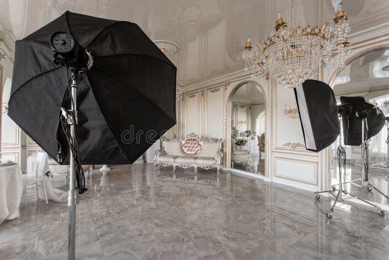 Het binnenland van de fotostudio klassieke luxueuze flats met een witte open haard, een bank, grote vensters en een kroonluchter stock foto's