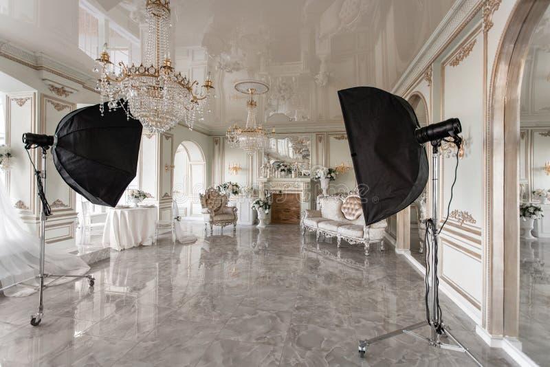 Het binnenland van de fotostudio klassieke luxueuze flats met een witte open haard, een bank, grote vensters en een kroonluchter royalty-vrije stock foto