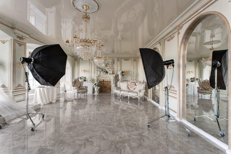 Het binnenland van de fotostudio klassieke luxueuze flats met een witte open haard, een bank, grote vensters en een kroonluchter royalty-vrije stock afbeelding