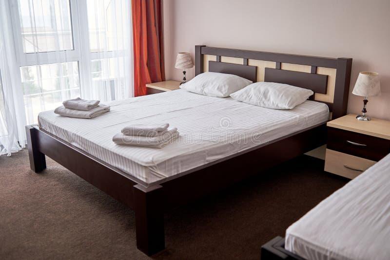 Het binnenland van de hotelslaapkamer met leeg tweepersoonsbed met houten hoofdeinde, bedlijst en groot venster, exemplaarruimte  stock afbeelding