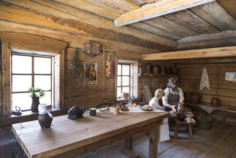 Het binnenland van de hut van een landelijke ingezetene van het Siberische dorp van de 19de eeuw van de tweede helft Aardewerkles royalty-vrije stock afbeelding