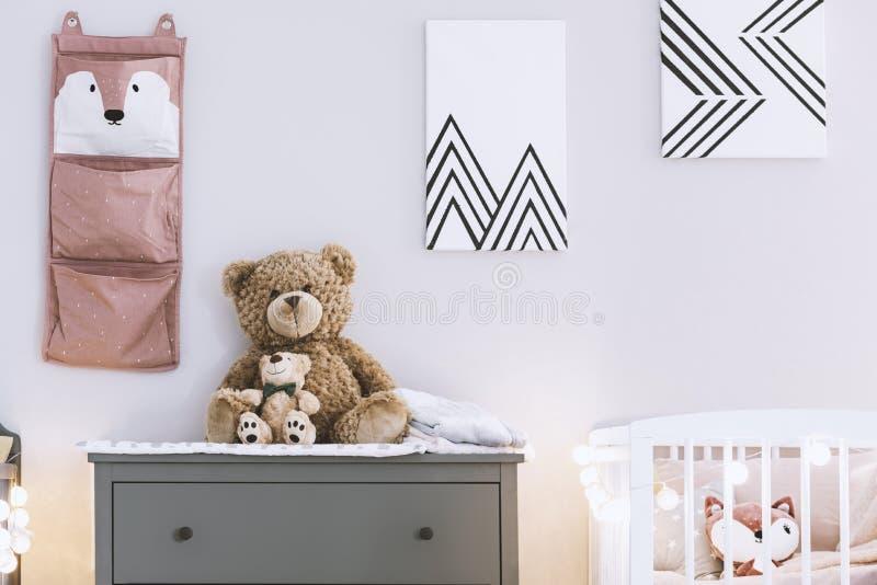Het binnenland van de jonge geitjesslaapkamer met elegante houten meubilair en affiches op de muur stock foto