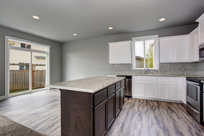 Het binnenland van de keukenruimte van een leeg huis Glasdeuren die de achtertuin overzien stock foto